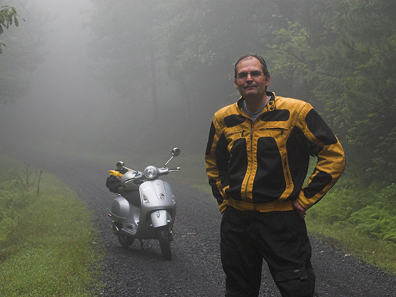 Steve Williams and Vespa GTS scooter on foggy forest road