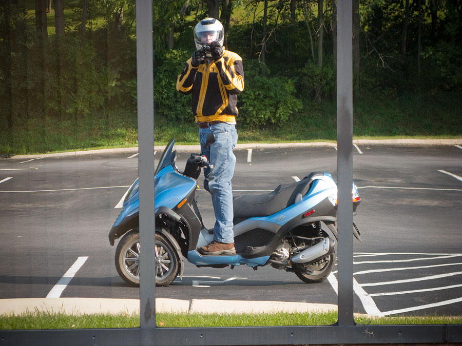 Steve Williams standing on Piaggio MP3 250 scooter
