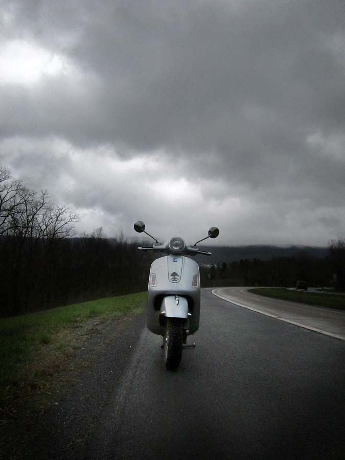 Vespa GTS scooter under a heavy grey sky