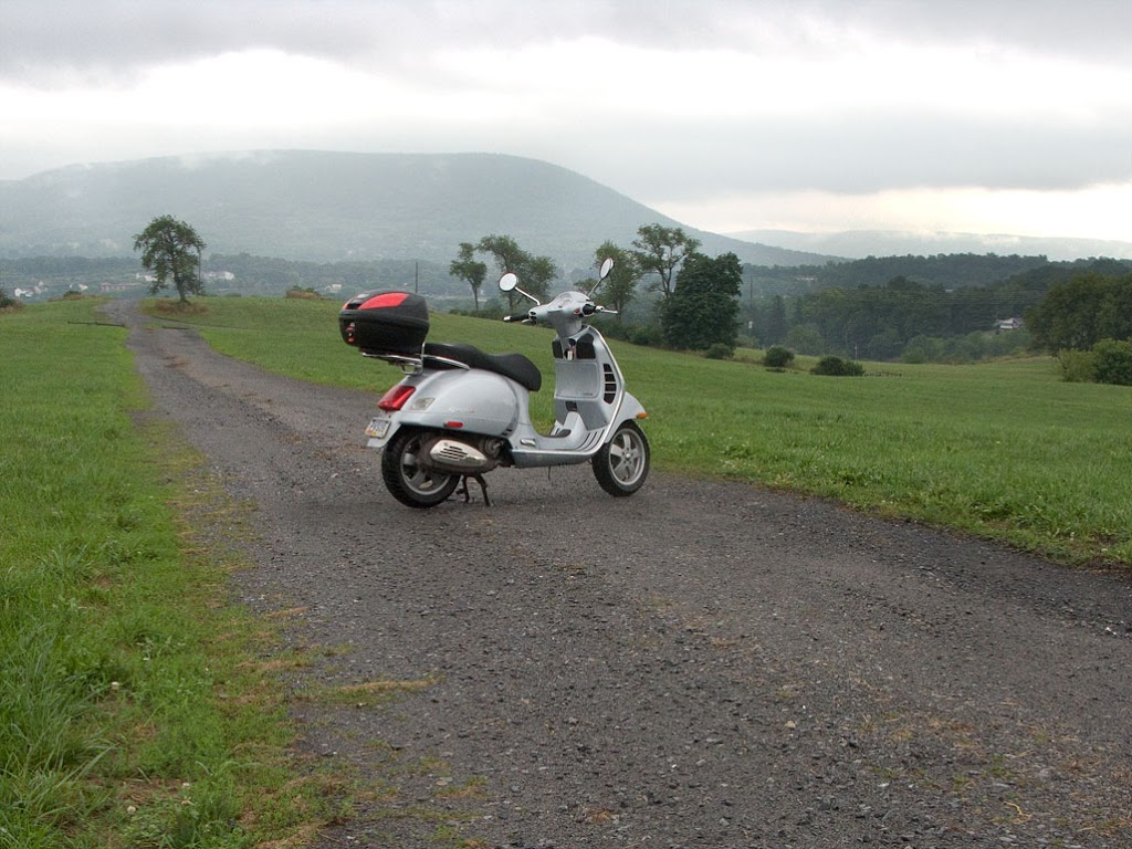 Vespa GTS scooter on gravel road after a clearing storm