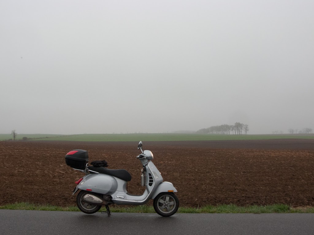 Vespa GTS scooter next to foggy farm field