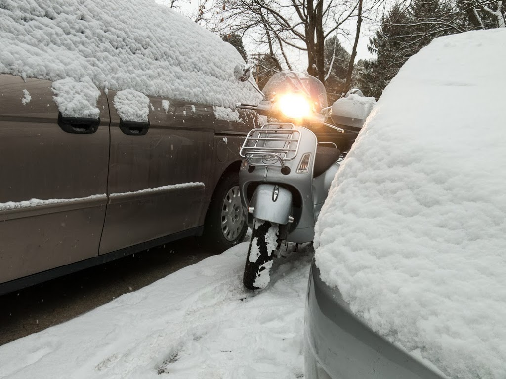 Vespa GTS scooter between snow covered cars