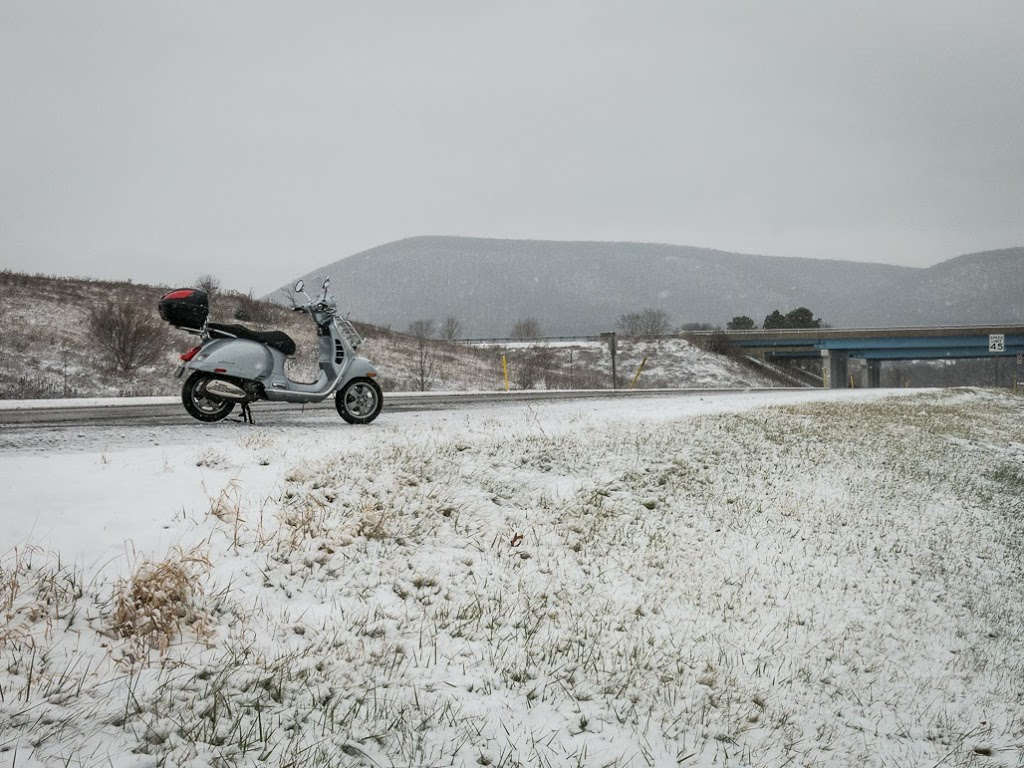 Vespa along snowy road with Mt. Nittany