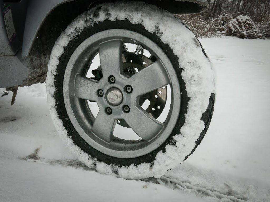 Winter tire on Vespa packed with snow