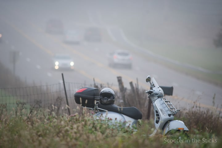 Vespa scooter along fog shrouded highway