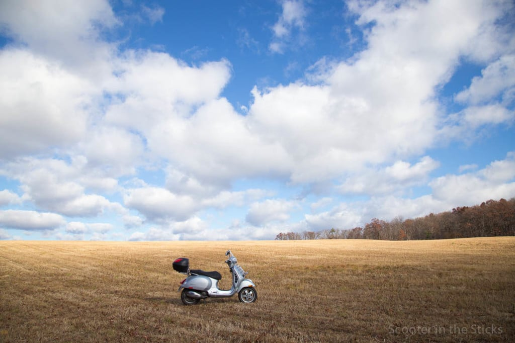 Vespa GTS 250 scooter in a field under a blue sky with clouds