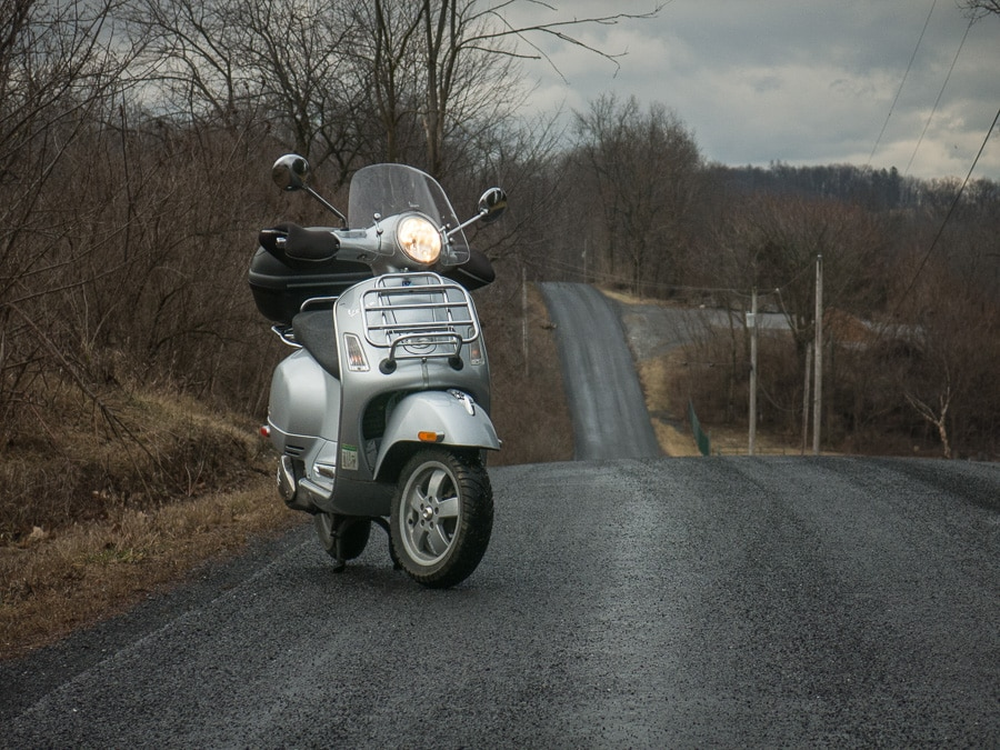 Vespa GTS scooter on wet rural road