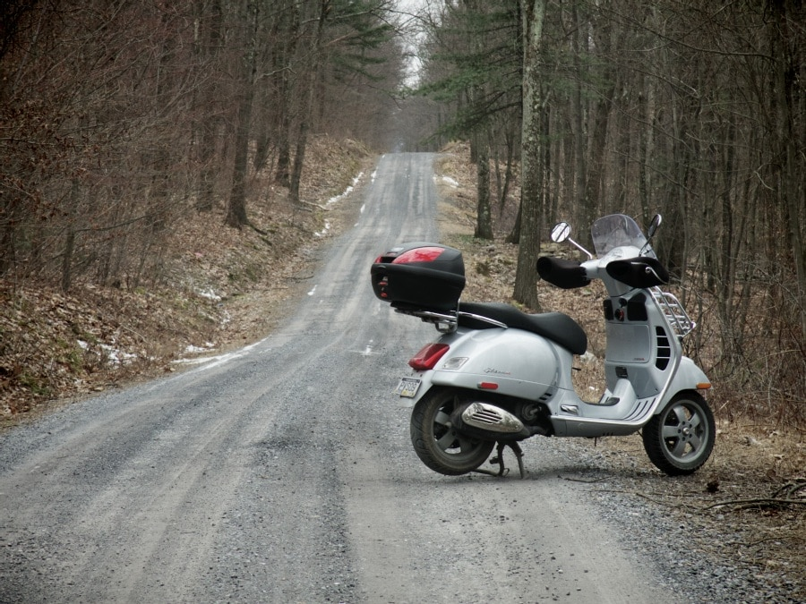 Vespa GTS scooter on forest road