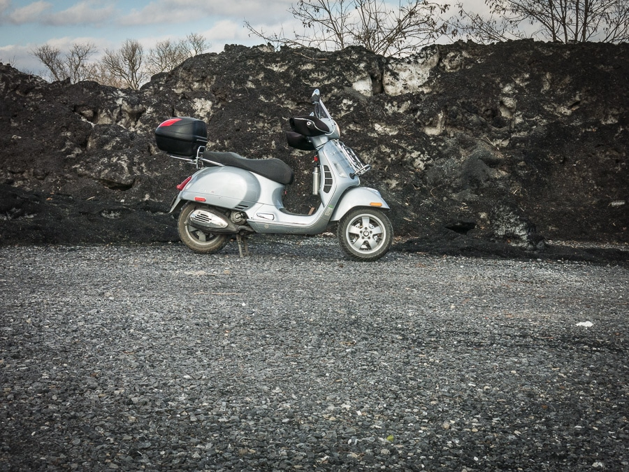 Vespa GTS scooter and pile of dirty snow and ice