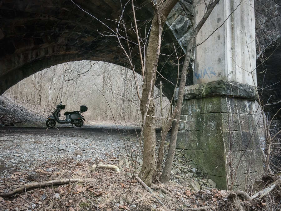 Scooter parked underneath a railroad bridge