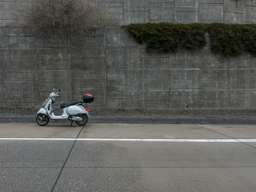 Vespa GTS scooter along highway wall
