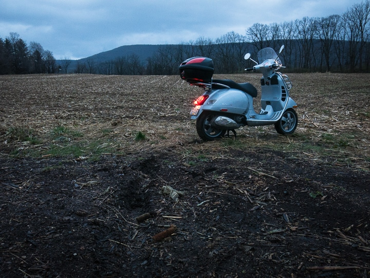 Vespa GTS scooter in muddy field at dusk