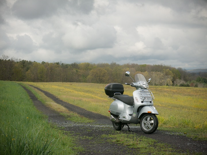Vespa GTS scooter along small farm lane