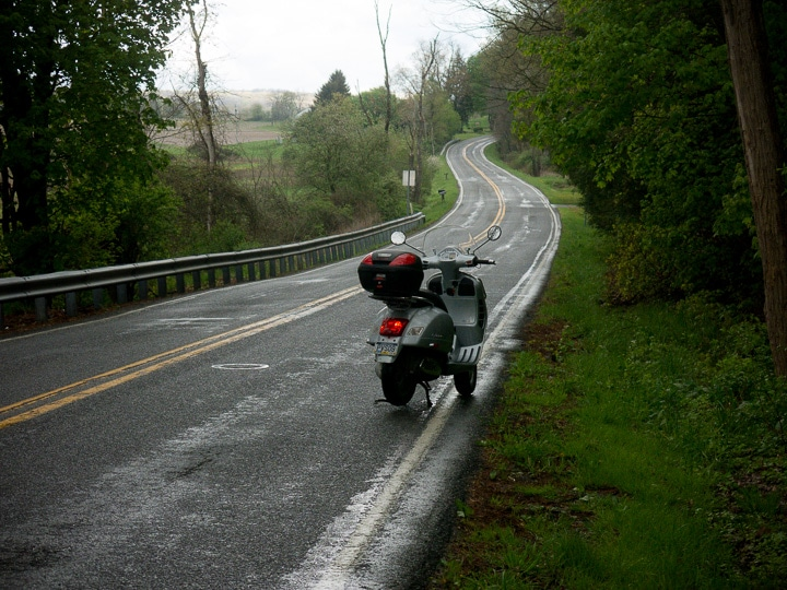 Vespa GTS scooter on a winding wet road