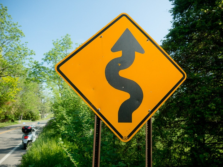 Winding road ahead sign with Vespa scooter in the background