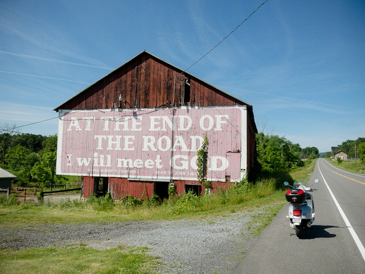 Vespa next to barn with biblical saying painted on it