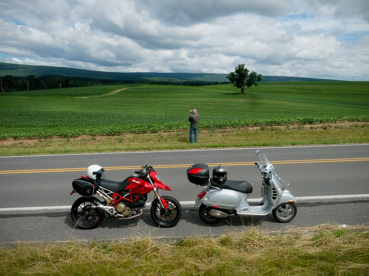 Ducati motorcyle and Vespa scooter together on a rural road