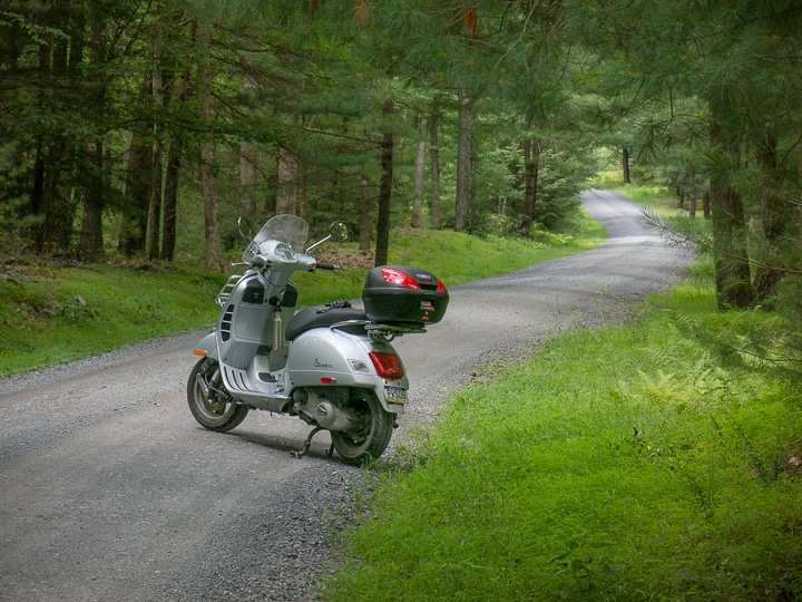 Vespa GTS scooter along gravel road in Rothrock State Forest