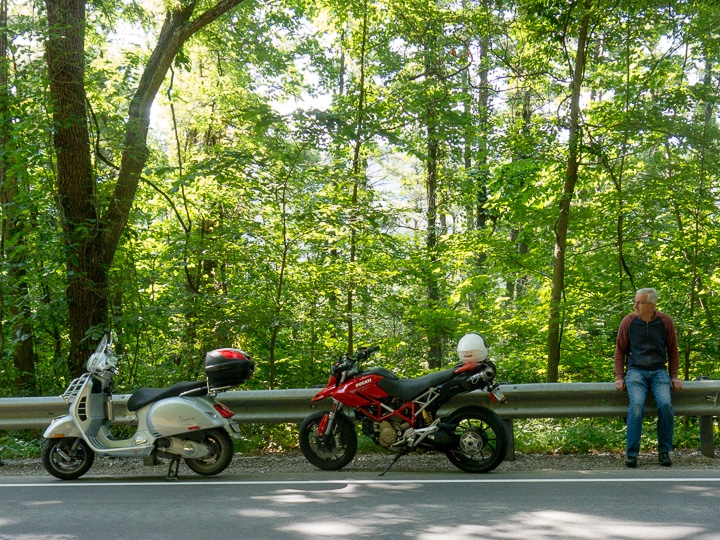 Vespa GTS and Ducati Hypermotard along a shady road