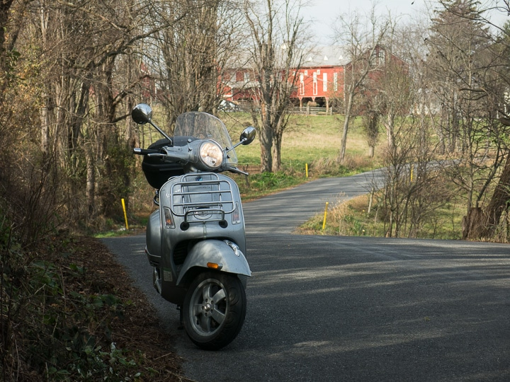 Vespa GTS scooter on rural road with red barn
