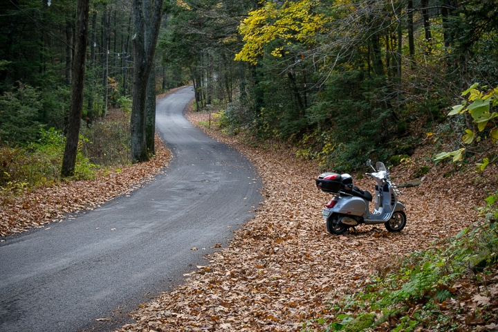 Vespa GTS on a winding road in autumn forest