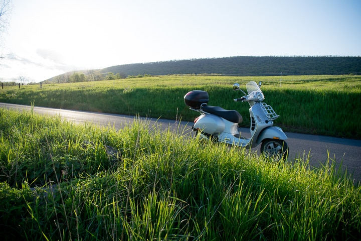 Vespa GTS scooter at sunset on a rural road