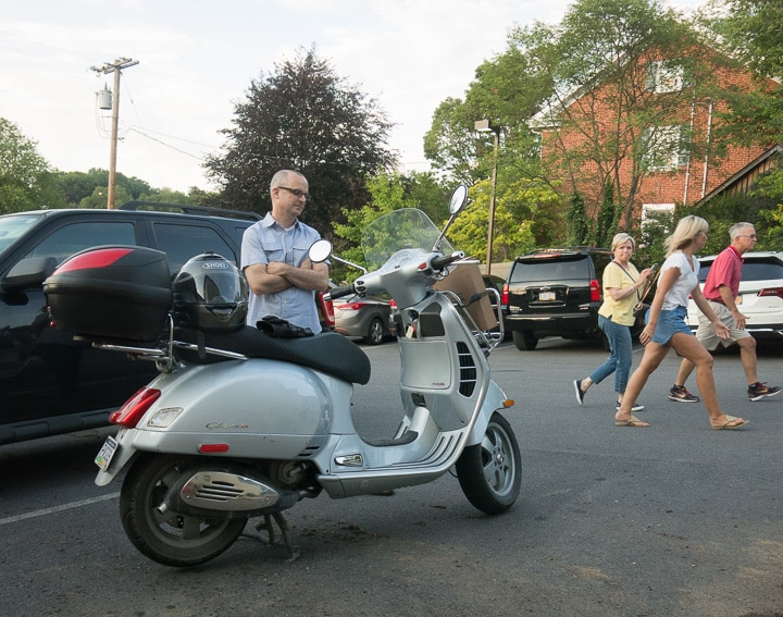 Jon Emigh looking at a Vespa GTS scooter
