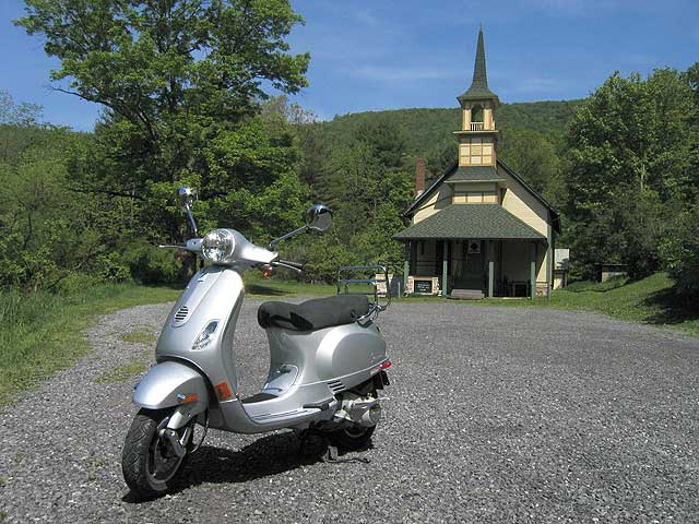 Vespa LX150 in front of old rural church