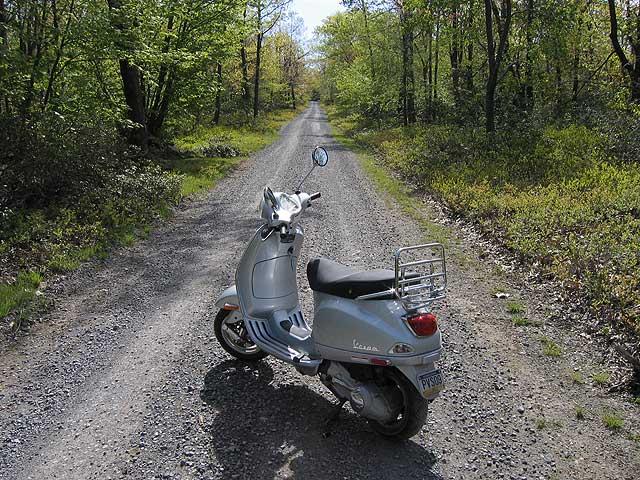 Vespa LX150 on gravel road in forest near Little Flat