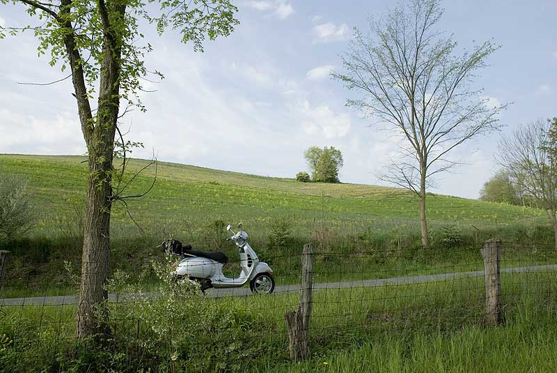 Vespa GTS scooter on a rural road in summer