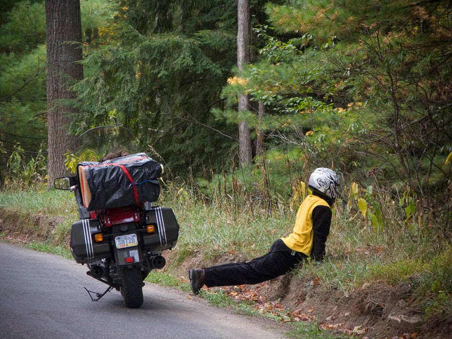 Paul Ruby stretching his back along road during motorcycle trip