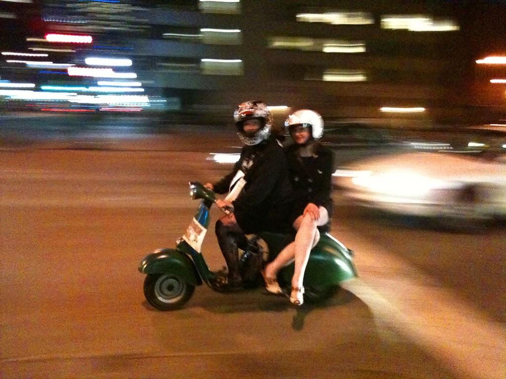 riding side-saddle on a vintage Vespa scooter at night in Denver