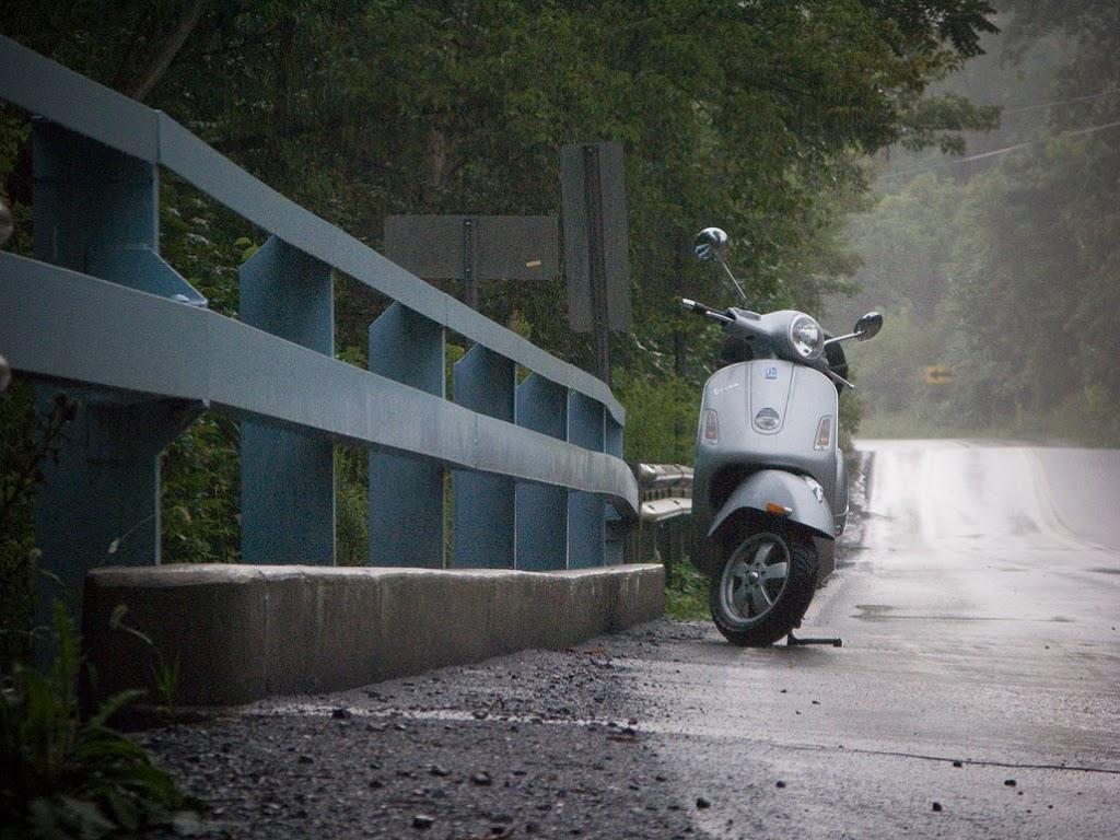Vespa GTS scooter on a bridge in the rain