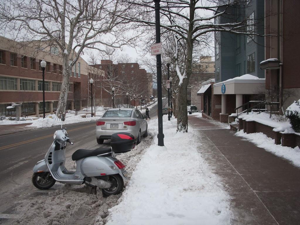 Vespa GTS scooter parked on snowy street