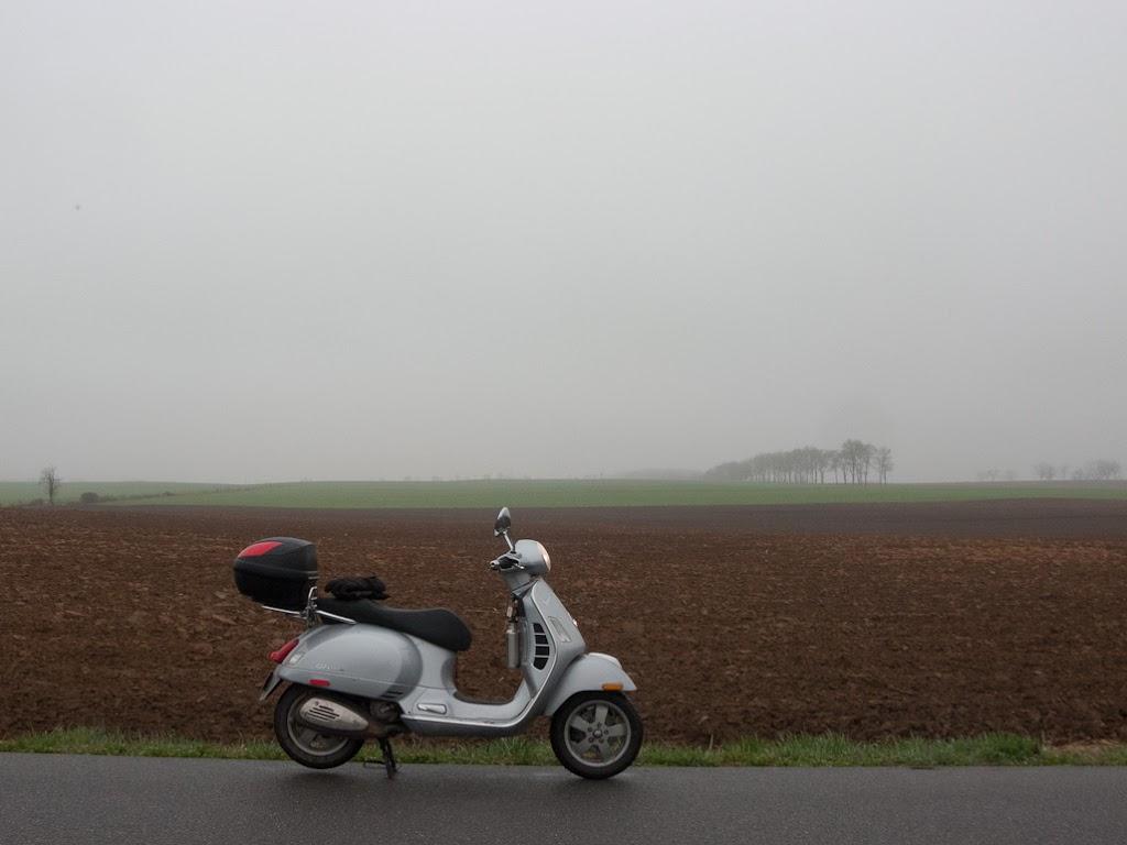 Vespa GTS scooter next to foggy farm field