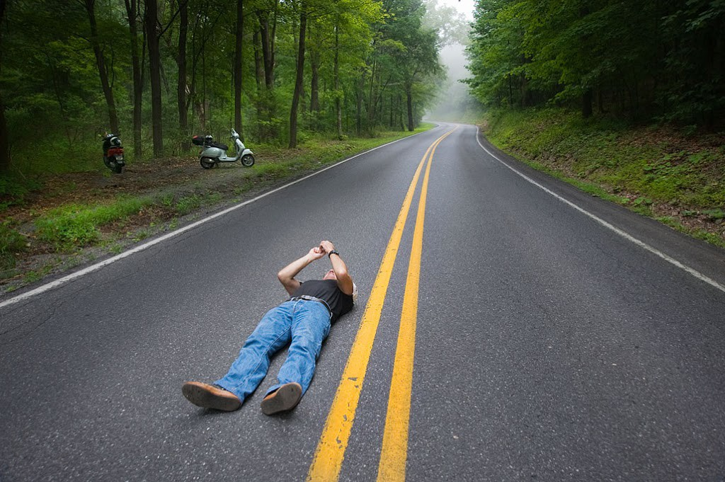 Man lying on a road along the center line