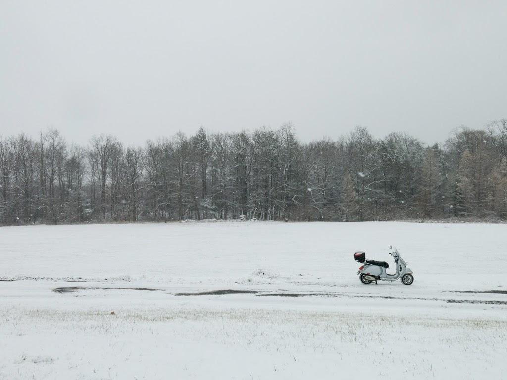 Vespa GTS scooter in snowy field
