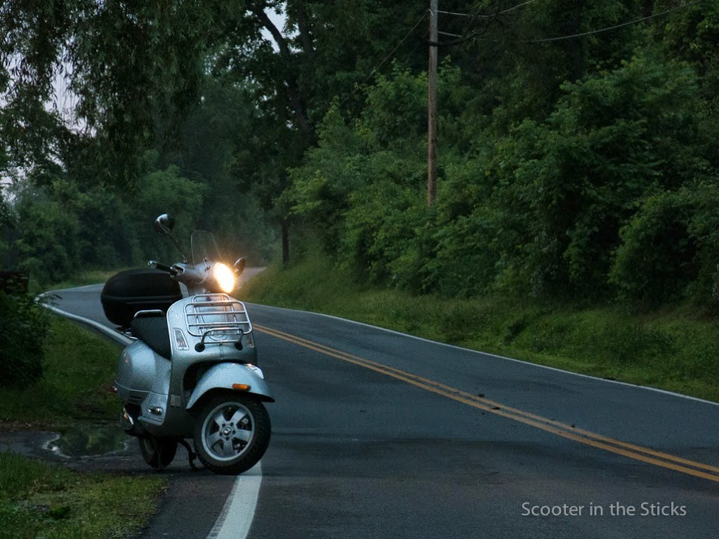 Vespa GTS scooter on rural road during an evening ride