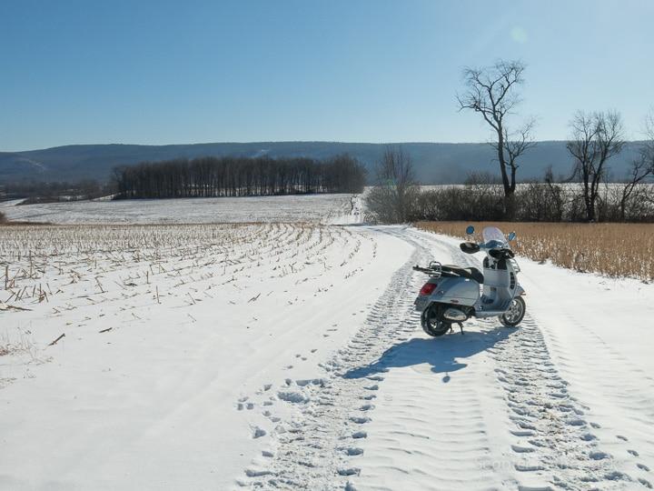 Vespa GTS 250 scooter on snowy farm lane