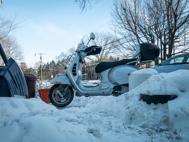 Vespa scooter on snow-covered driveway