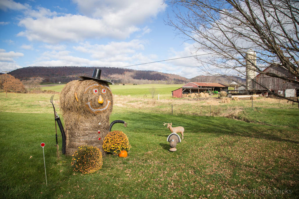 large pumpkin statue made of round hay bales