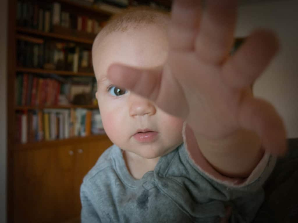 An infant reaching toward the camera