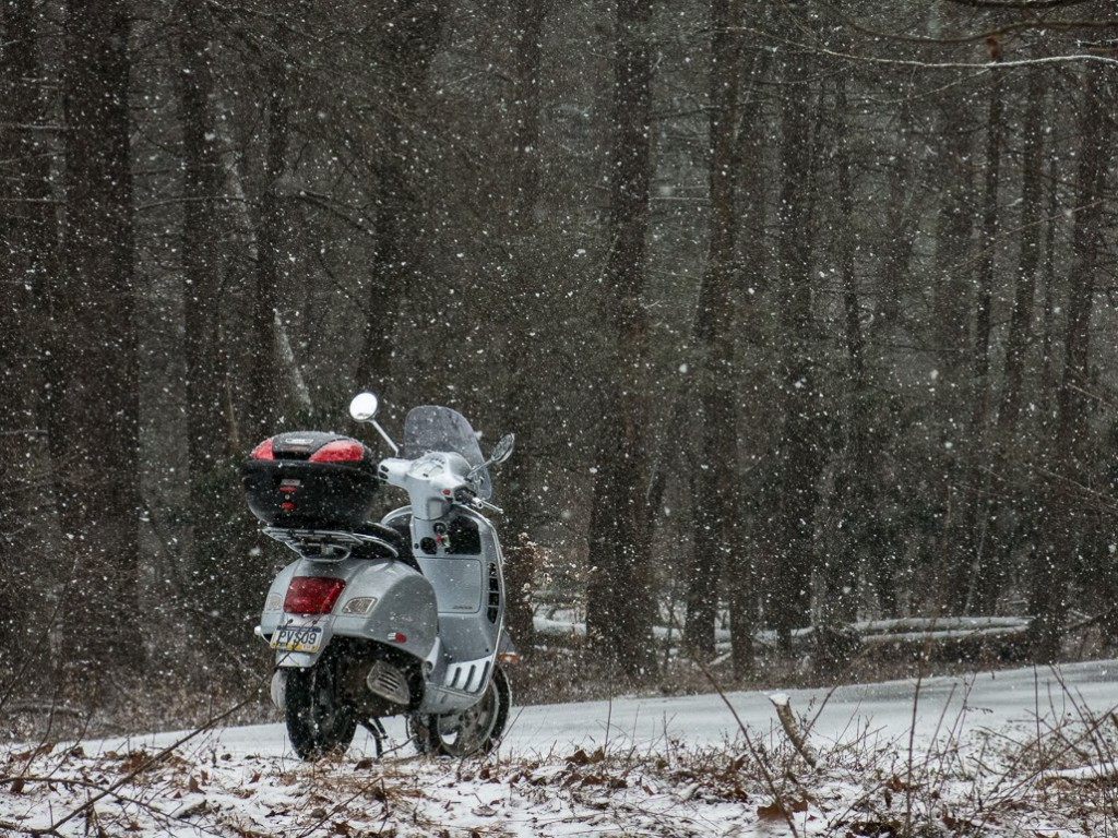 Vespa GTS scooter on snowy forest road