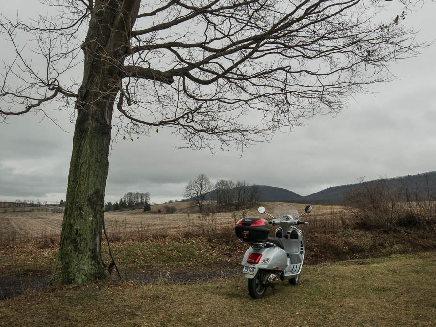 Vespa GTS scooter and farm landscape