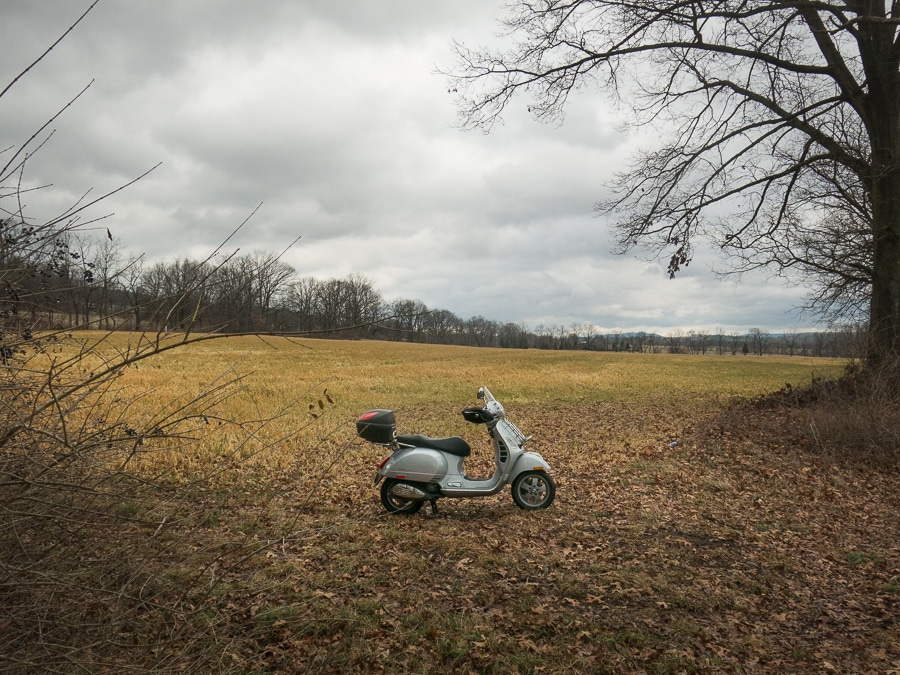 Vespa GTS scooter in a farm field on a rainy day