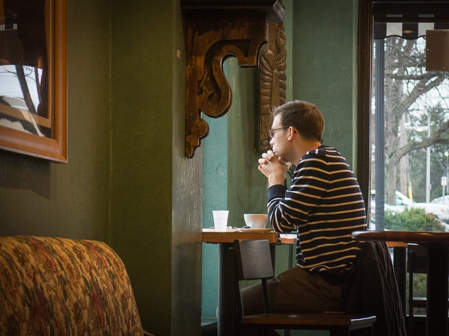 Man sitting in coffee shop looking out window