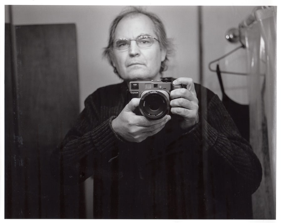 Steve Williams reflected in a mirror with a Mamiya 7 camera thinking about film vs. digital photography