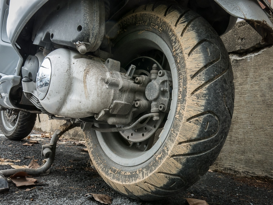 mud on the rear wheel of a Vespa GTS scooter
