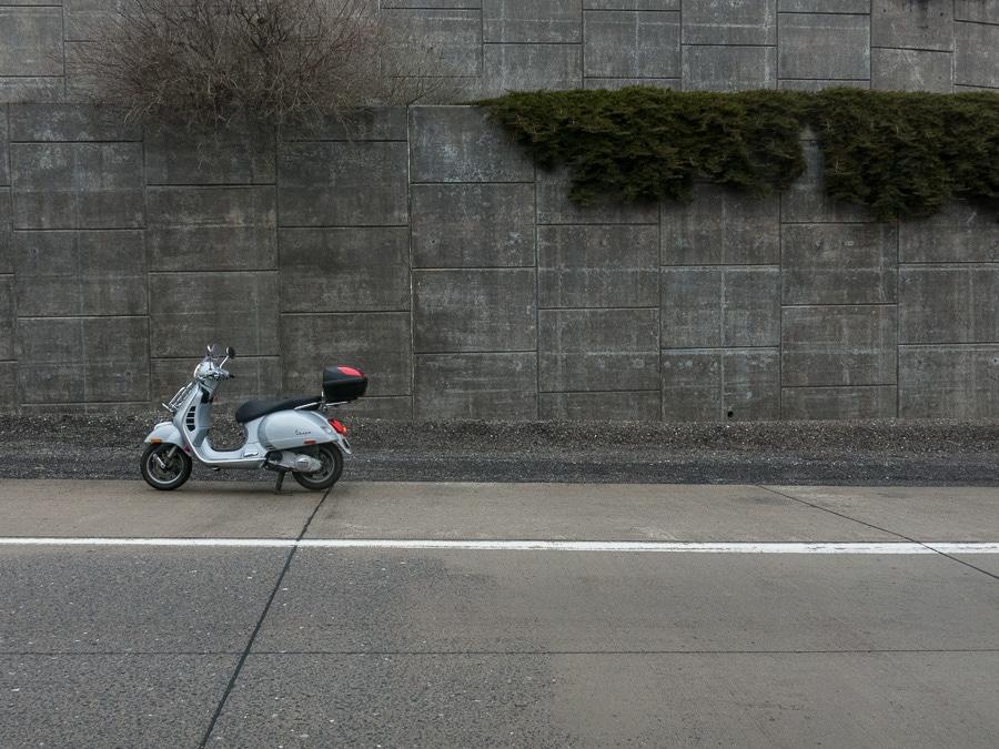Vespa GTS scooter along highway wall