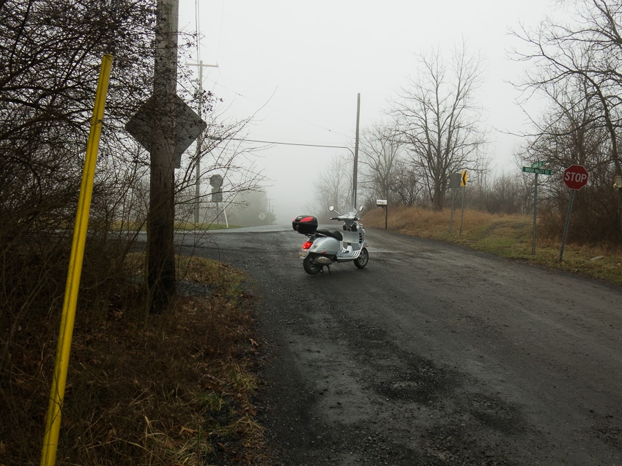 Vespa at a rural intersection on a foggy morning